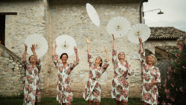 Bridesmaids having fun with umbrellas